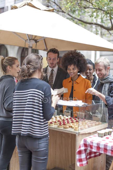 Людей, які купують тістечка харчова ларьок у міський ринок — стокове фото