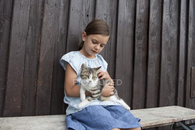 Linda chica con gato sentado en la banca - foto de stock