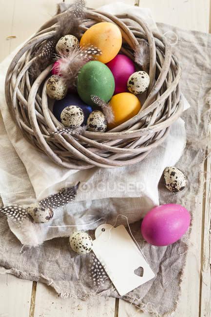 Colorful Easter eggs and quail eggs in rustic nest — Stock Photo