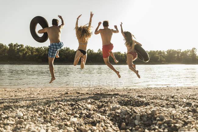 Freunde mit Schläuchen springen am Strand in Fluss — Stockfoto