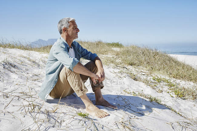 Relaxed caucasian best ager man at the beach — Stock Photo