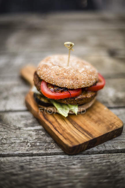 Homemade veggie burger with aubergine, lettuce, tomato and onion on chopping board — Stock Photo