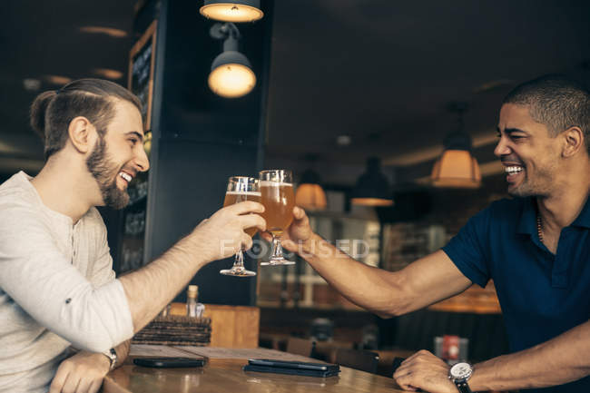 Two happy men in a bar clinking beer glasses — Stock Photo
