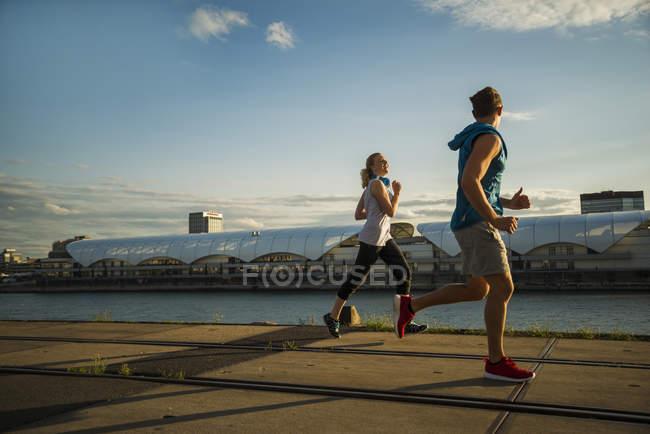 Jeune couple courant au bord de la rivière en ville — Photo de stock