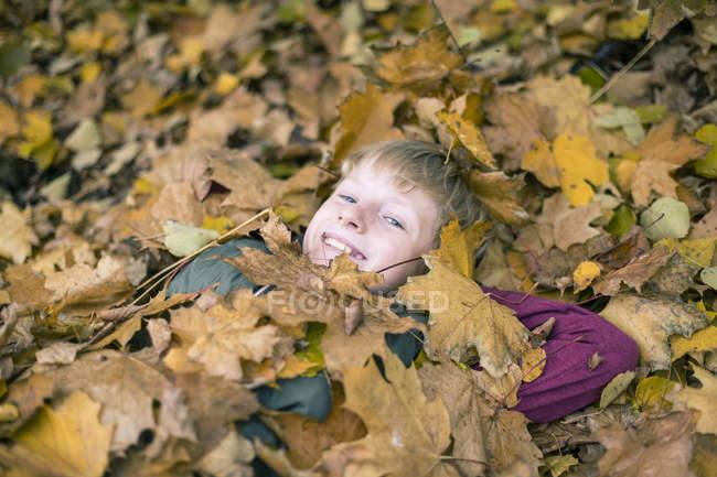 Porträt eines lächelnden Jungen, der mit Herbstblättern bedeckt auf dem Boden liegt — Stockfoto