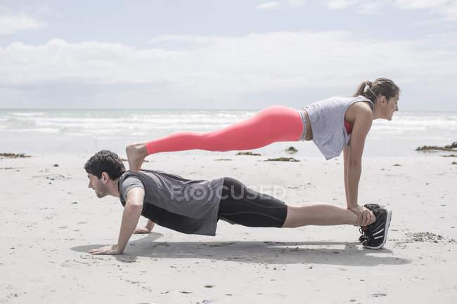 Jovem e mulher exercitando na praia — Fotografia de Stock