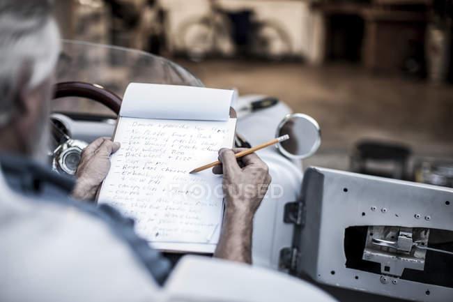 Homem sênior com lista de verificação no carro esportivo — Fotografia de Stock