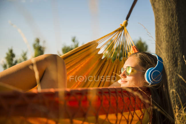 Frau mit Sonnenbrille und Kopfhörer zum Entspannen in der Hängematte — Stockfoto