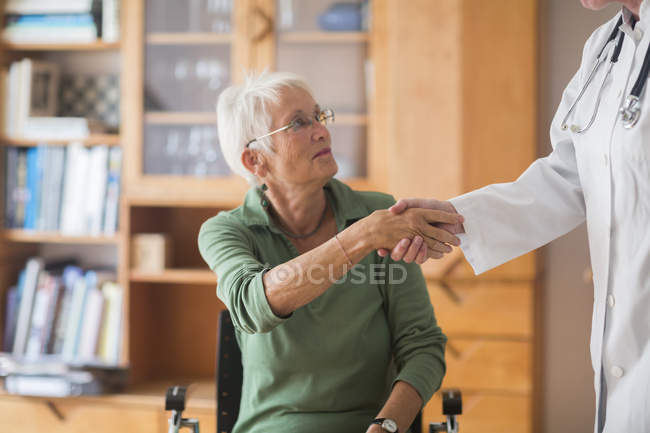 White haired senior woman shaking hands with her doctor — Stock Photo