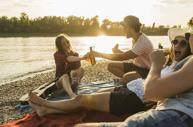 Friends relaxing at the riverside at sunset — Stock Photo