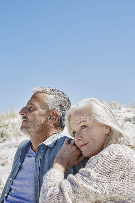 Mature Couple embracing at the beach — Stock Photo