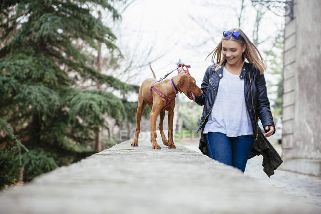 Serbia, Petrovaradin, smiling young woman with her dog — Stock Photo