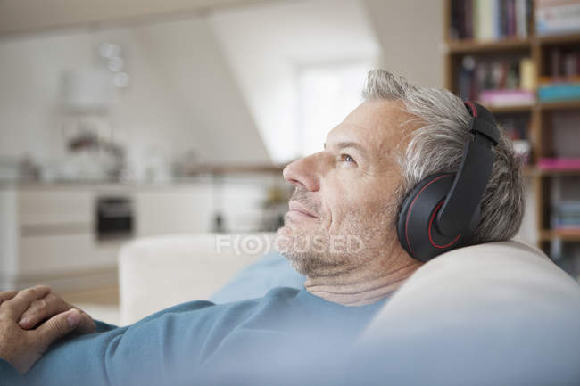 Relaxed man wearing headphones listening to music at home — Stock Photo