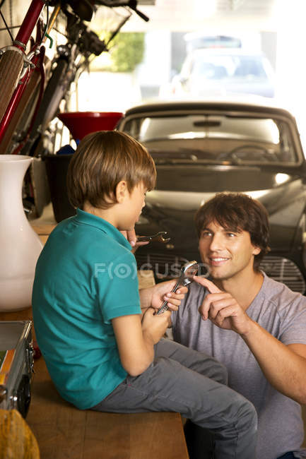 Father and son in garage with vintage car and tools — Stock Photo