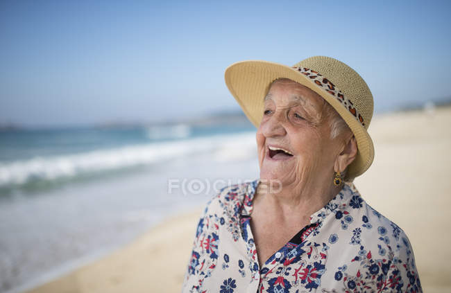 Portrait of laughing senior woman on the beach — Stock Photo