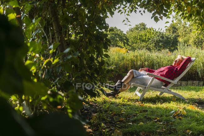 Старшая женщина отдыхает в садовом кресле — стоковое фото