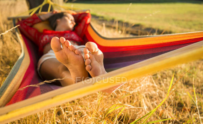 Feet of woman relaxing in a hammock — Stock Photo