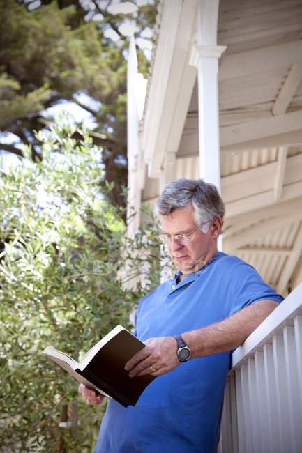 Man leaning against balustrade reading a book — Stock Photo
