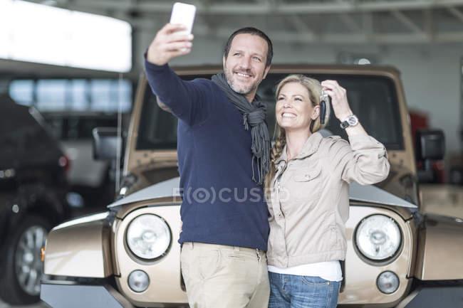Счастливая пара в автосалоне делает селфи перед новой машиной — стоковое фото
