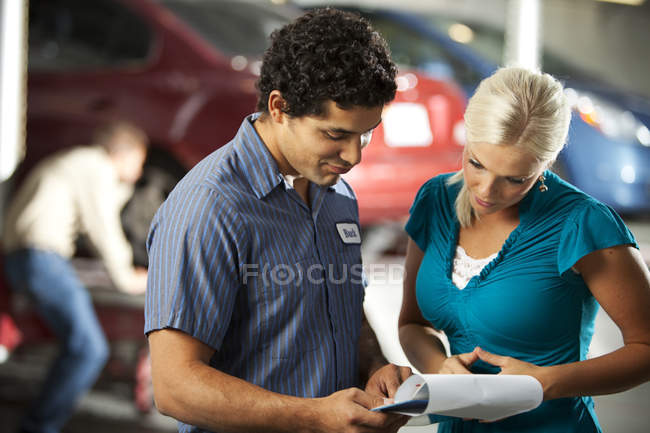 Man and customer in repair garage looking at check list — Stock Photo