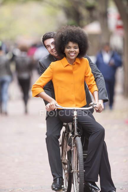 Coppia felice in bicicletta in una città — Foto stock
