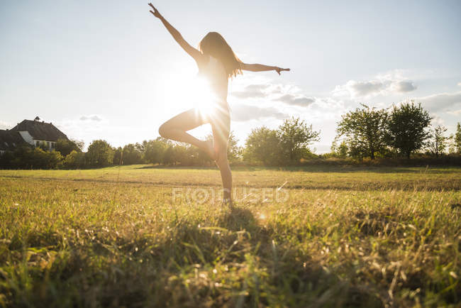 Back view of woman standing on one leg on a meadow at backlight — Stock Photo