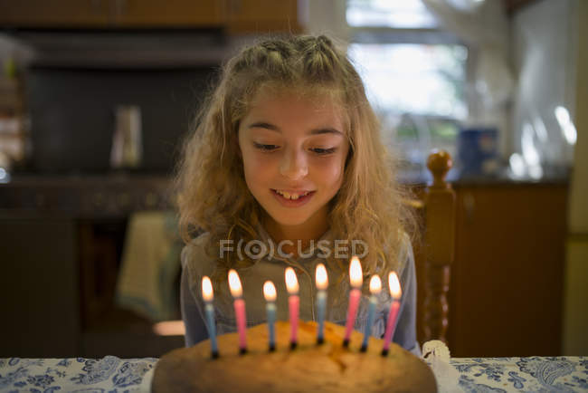 Portrait of little girl looking at candles on her birthday cake — Stock Photo