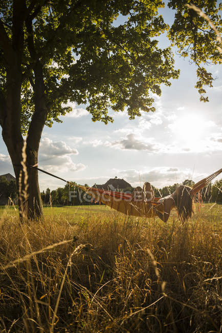 Woman lying in a hammock relaxing in nature — Stock Photo
