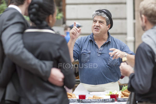 Food seller at city market talking to customers — Stock Photo