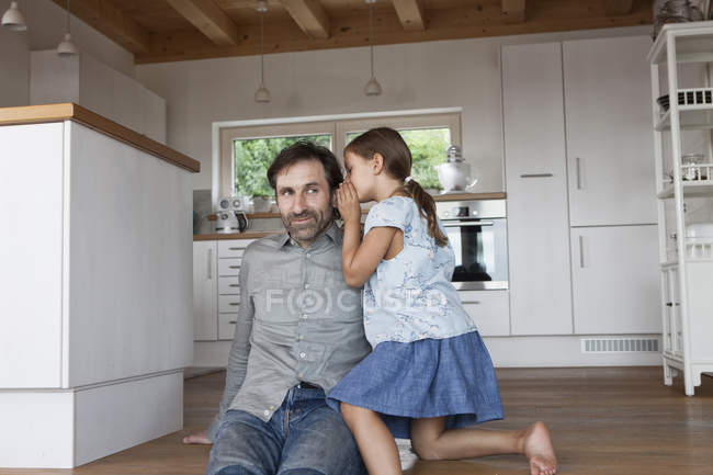 Father sitting on kitchen steps, daughter whispering into his ear — Stock Photo