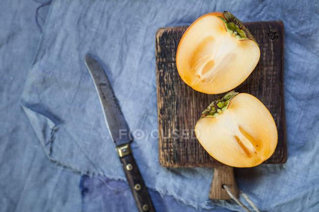 Vue de kaki en tranches sur une planche de bois — Photo de stock