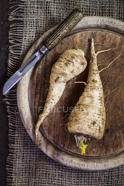 Parsley roots and peeler on wooden board and jute — Stock Photo