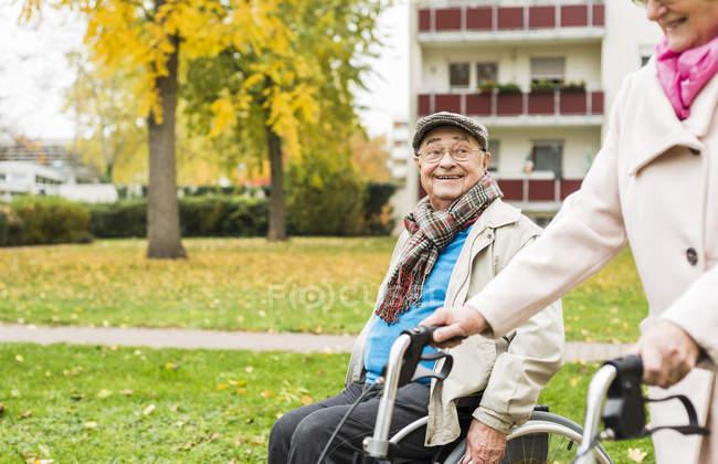Старшие женщины с колесных Уокер и старший человек в инвалидной коляске на открытом воздухе в осень — стоковое фото