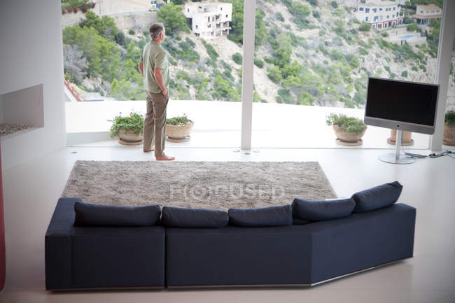 Spain, Mallorca, man standing in his living room looking through the window — Stock Photo