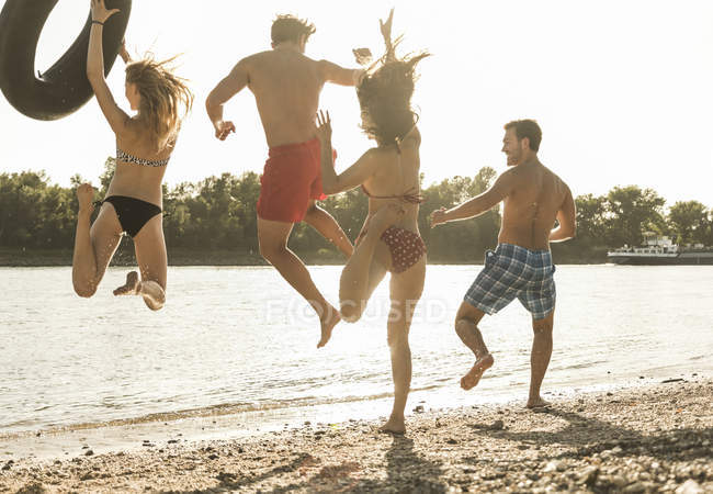 Friends with inner tube jumping into river on beach — Stock Photo