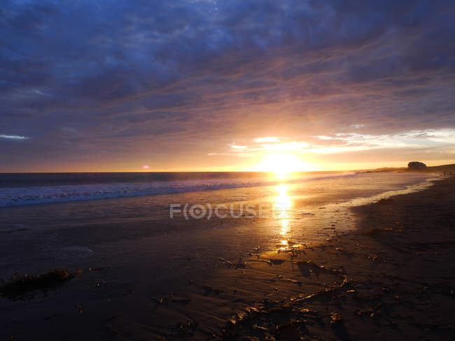 Distant view of sandy beach and cloudy sky at sunset — Stock Photo