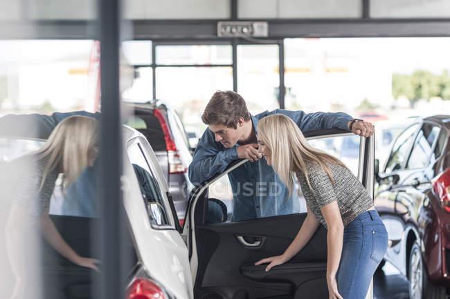Молодая пара осматривает новую машину в автосалоне — стоковое фото