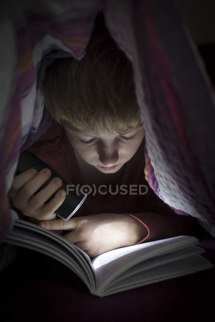 Boy with torch reading book under a blanket — Stock Photo