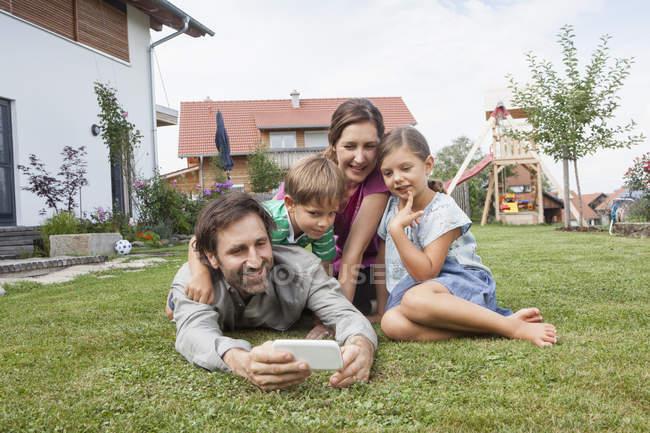 Família sorridente de quatro no jardim com telefone celular — Fotografia de Stock