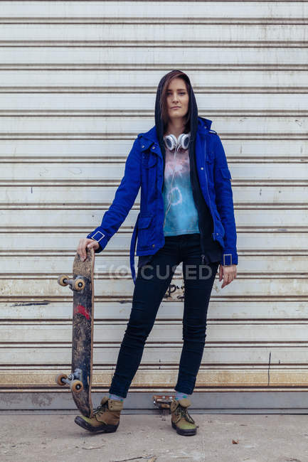 Portrait of young woman with skateboard — Stock Photo