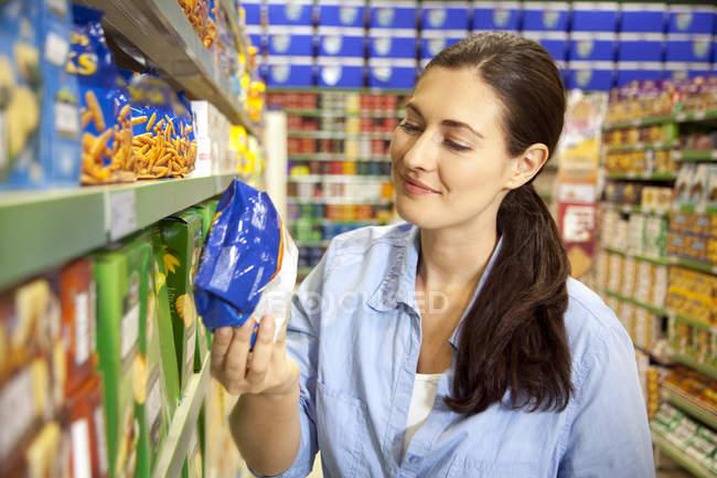 Улыбающийся клиент смотрит на упаковку в супермаркете — стоковое фото
