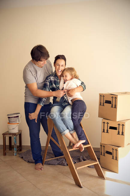 Happy family on step ladder beside cardboard boxes — Stock Photo