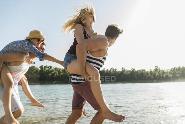 Due giovani coppie giocose che si divertono al fiume — Foto stock