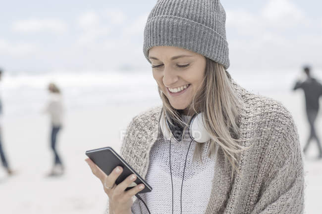 Portrait of smiling woman wearing beanie looking at smartphone on the beach — Stock Photo