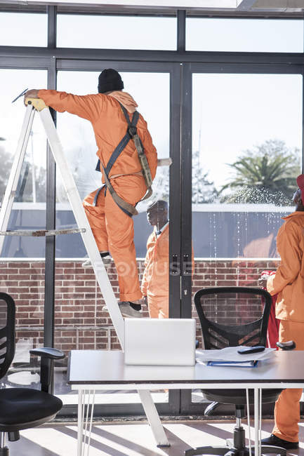 Window cleaners working in modern office — Stock Photo
