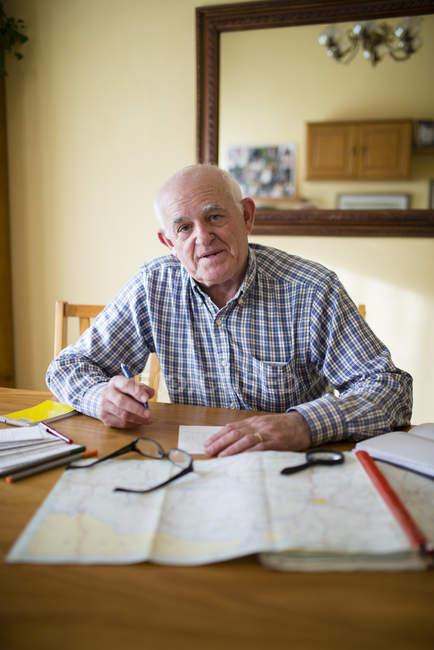 Portrait of senior man with road map planning a trip — Stock Photo