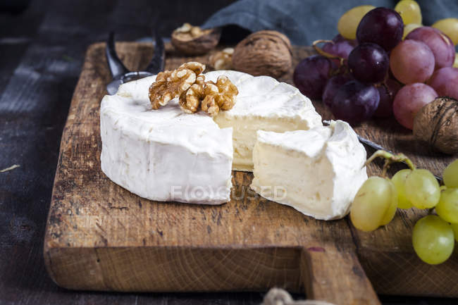 Wooden board with sliced camembert, walnuts and grapes — Stock Photo