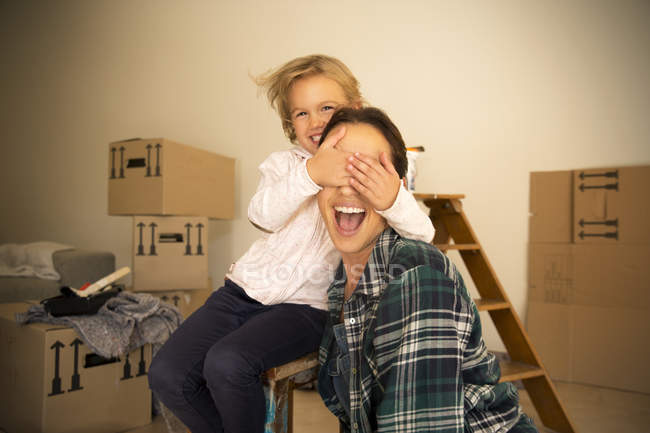 Daughter covering mothers eyes with cardboard boxes on background — Stock Photo
