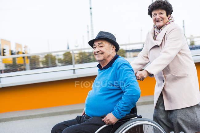 Старші жінки натисканням чоловіка в інвалідному візку — стокове фото