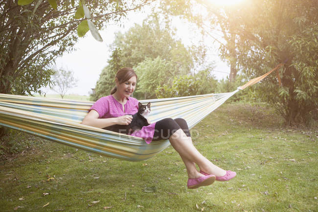 Relaxed caucasian woman with cat in hammock — Stock Photo